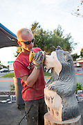 Darin Finnigan sands a wooden black bear sculpture after Ray Schulz sculpts the log with a chainsaw.  Schulz visited Black Bear Diner in Milpitas, Calif. on July 11, 2012 to demonstrate the chainsaw carving process of wooden statues found at every diner.  Photo by Stan Olszewski/SOSKIphoto.