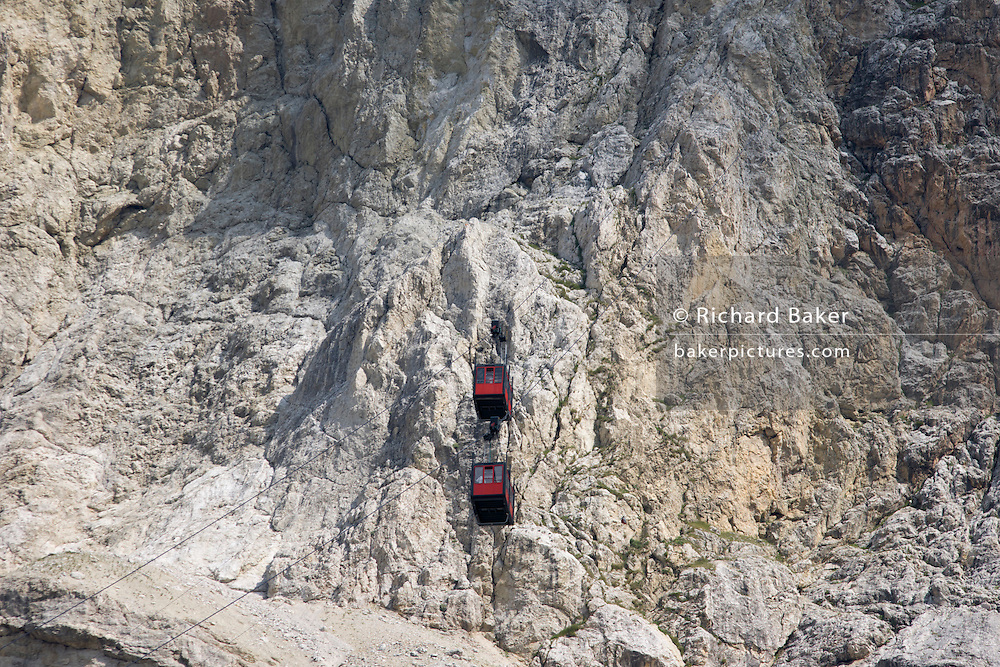 From Passo Falzarega (Pass), two cable car gondolas pass each other on the rock face of Lagazuoi (3,244 m), a Dolomites mountain in south Tyrol, Italy. One of two gondolas rises to the Lagazuoi (2,835), which was the object of heavy combat in World War I. Lagazuoi is a mountain in the Dolomites of northern Italy, lying at an altitude of 2,835 metres (9,301 ft), about 18 kilometres (11 mi) southwest by road from Cortina d'Ampezzo in the Veneto Region. It is accessible by cable car and contains the Refugio Lagazuoi, a mountain refuge situated beyond the northwest corner of Cima del Lago. The mountain range is well known for its wartime tunnels.