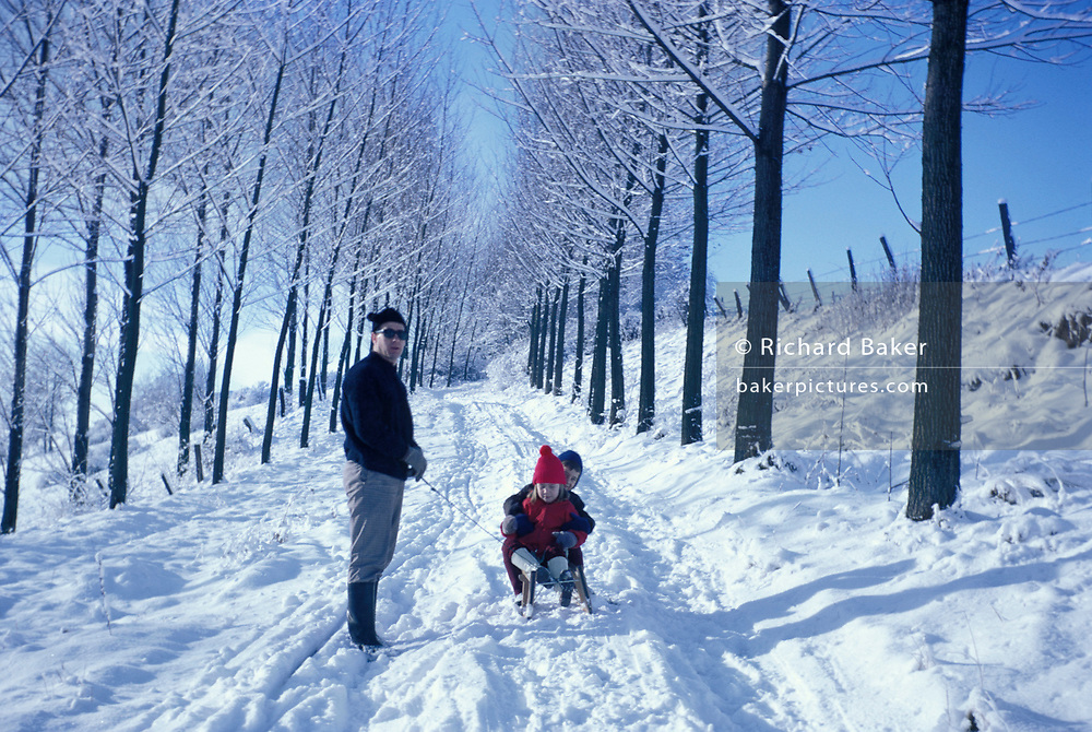 A father pulls his young children along in the snow of a rural tree-lined avenue in rural Germany in the late-1960s, on 13th December 1969, in Bielefeld, Germany