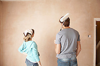 Couple looking at wall of unrenovated room back view
