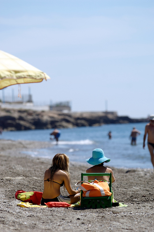 Tourists sunbathe on the beach at Torrox Costa on the Costa del Sol, Spain