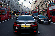 A black BMW diplomatic car is illegally parked in the middle taxi lane normally reserved for London taxi cabs.