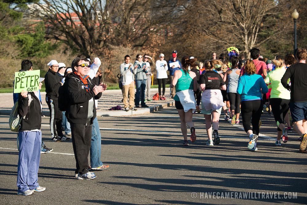 Spectators cheer on runners in the Cherry Blossom 10-miler in Washington DC. The Cherry Blossom 10-Miler (formally the Credit Union Cherry Blossom 10 Mile Run) is held each spring during the National Cherry Blossom Festival and attracts tends of thousands of runners.