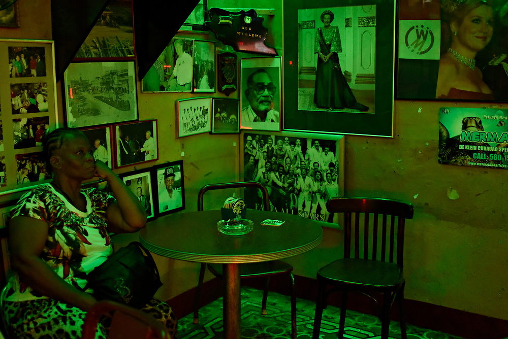 WILLEMSTAD, CURACAO - DECEMBER 12, 2014: Established in 1954, one of Curacao's oldest bars, the Netto Bar in Otrobanda, is a popular local watering hole, discovered by tourists and visited by Dutch royalty. It's decorated with pictures of Dutch King Willem-Alexander and Dutch soccer paraphernalia and known for it's Rom Berde (green run served with coconut water). (photo by Melissa Lyttle)