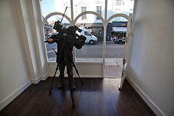 "© Licensed to London News Pictures. 11/12/2013. London, United Kingdom. A television cameraman films an empty wall where the paintings hung. The gallery ""Exhibitionist"" in 15b Blenheim Crescent London. Two of artist Damien Hirst's paintings were stolen from the gallery. Photo credit : Andrea Baldo/LNP"