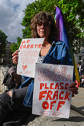 © Licensed to London News Pictures. 09/06/2017. London, UK. A woman carries two signs, one for Jeremy Corbyn and one against Theresa May.  Anti-Tory protesters demonstrate outside Downing Street on the day that the General Election results produced a hung Parliament.  A variety of different groups, from LGBT supporters to Save the NHS supporters, gathered to make their views heard. Photo credit : Stephen Chung/LNP