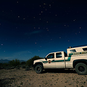 Immigration along the USA-Mexico border-  A U.S. border patrol agent sits in his truck and monitors the border for undocumented workers in Arizona.