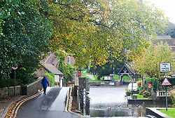 ©Licensed to London News Pictures 15/10/2019<br /> Eynsford,UK. A lady walking her dog over Eynsford bridge. A grey and wet autumnal morning in Eynsford, Kent. Photo credit: Grant Falvey/LNP