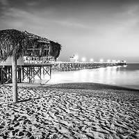 San Clemente California pier and tiki umbrella at night black and white photo. San Clemente California is a popular coastal beach city in the United States of America. Copyright ⓒ 2017 Paul Velgos with all rights reserved.