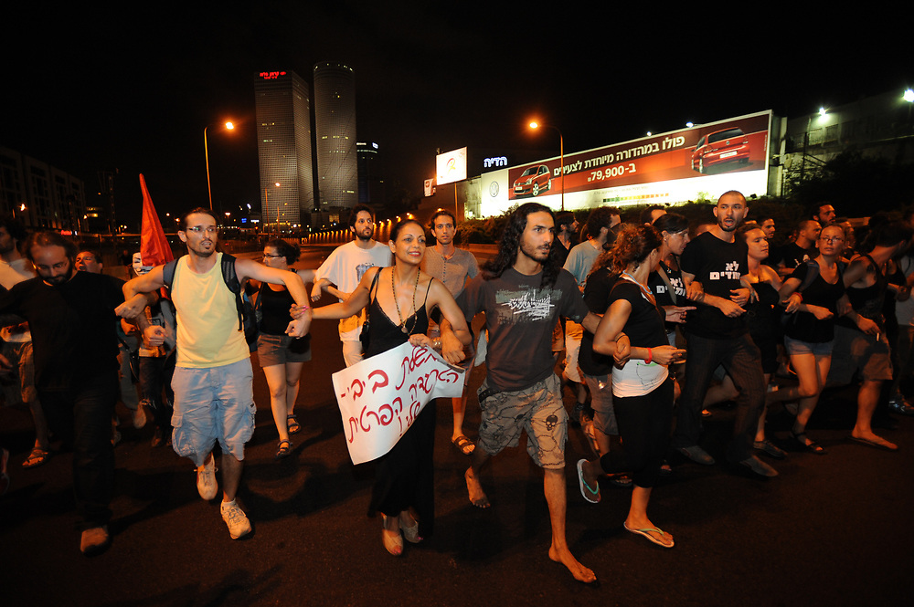 Israelis are blocking Ayalon Highway, one of Israel's main roads, during a demonstration in Tel Aviv on July 21, 2012, in memory of Moshe Silman, an Israeli protester who set himself alight during a social justice demonstration on July 14. Silman struggled for his life after suffering from extensive burns and died at Tel Hashomer hospital near Tel Aviv, on July 20. Photo by Gii Yaari
