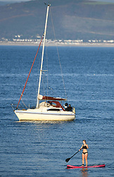 © Licensed to London News Pictures. 13/09/2020. Swansea, UK. A women sails along a calm sea off the coast of Mumbles, Swansea with a sail boat in the background on a beautiful evening in south Wales. The UK enjoyed a fine weekend of warm and sunny weather. Photo credit: Robert Melen/LNP