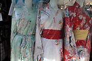 kimono like dresses wrapped in plastic at an outdoors open market stall Japan
