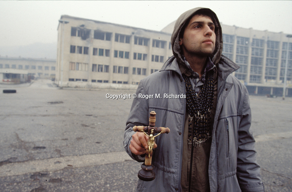 A man selling crucifixes outside the destroyed train station looks up at the sound of an artillery shell explosion nearby, Sarajevo, Bosnia-Herzegovina, December 1992. PHOTO BY ROGER M. RICHARDS