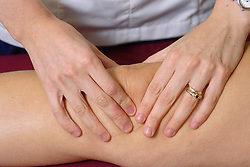 Closeup of physiotherapist assessing patient's knee joint,