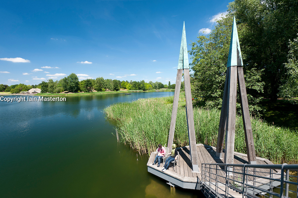 Visitors sitting on wooden footbridge crossing lake at Britzer Garden in Neukolln in Berlin Germany