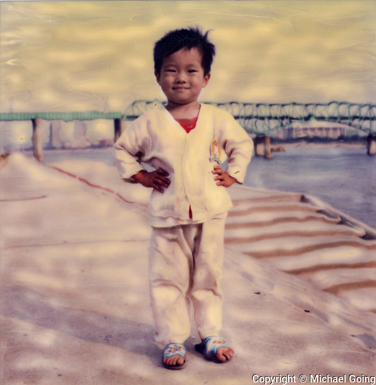 Altered Polaroid of little boy wth hands on hips standing by Han River, Seoul Korea