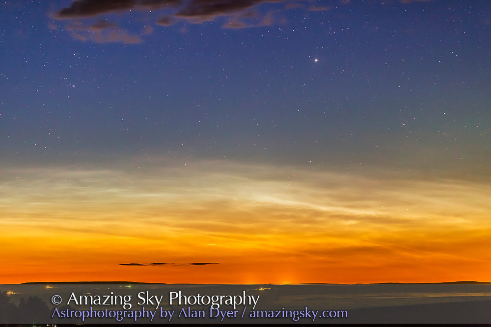A display of noctilucent clouds, the first seen from home in Alberta during the 2017 season, on June 23/24, 2017. This was a 12:43 am and the white NLCs mix with the colours of the perpetual twilight. Capella is the bright star at right of centre, circumpolar from this latitude of 51&deg; North.<br /> <br /> This is with the 135mm telephoto and is the first frame from a 370-frame time-lapse. It is 5 seconds at f/2 and ISO 800.