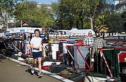 © Licensed to London News Pictures. 05/05/2018. London, UK. A jogger makes his way along the canal towpath during the Canalway Cavalcade festival in Little Venice, West London on Saturday,  May 5th 2018. Inland Waterways Association's annual gathering of canal boats brings around 130 decorated boats together in Little Venice's canals on May bank holiday weekend. Photo credit: Ben Cawthra/LNP