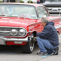 Paul Banfi of Mobil Alabama polishes the chrome rims of his 1060 Chevy Impala just after arriving at the BancorpSouth Arena for the Blue Suede Cruise on Friday.