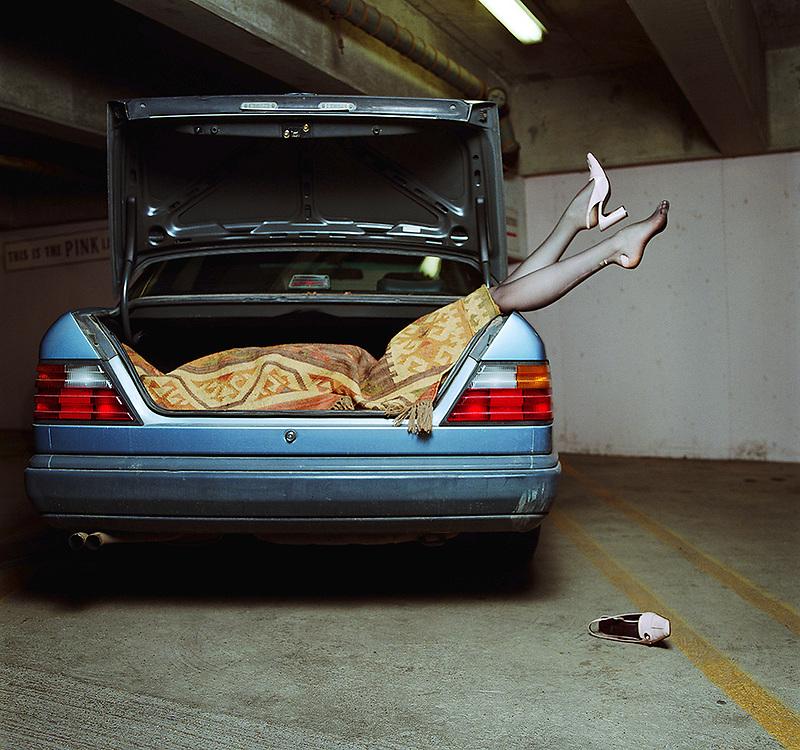 Woman wrapped in blanket, lying in car trunk