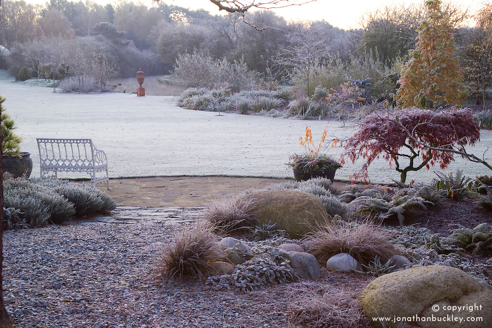 Frosty winter morning in John Massey's garden. View from bench towards urn and canal