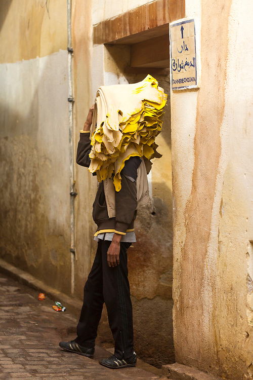 FEZ, MOROCCO - 3rd DECEMBER 2016 - Workers carry dried animal hides (skins) to the Chouwara Tannery through the old Fez Medina, Middle Atlas Mountains, Morocco.