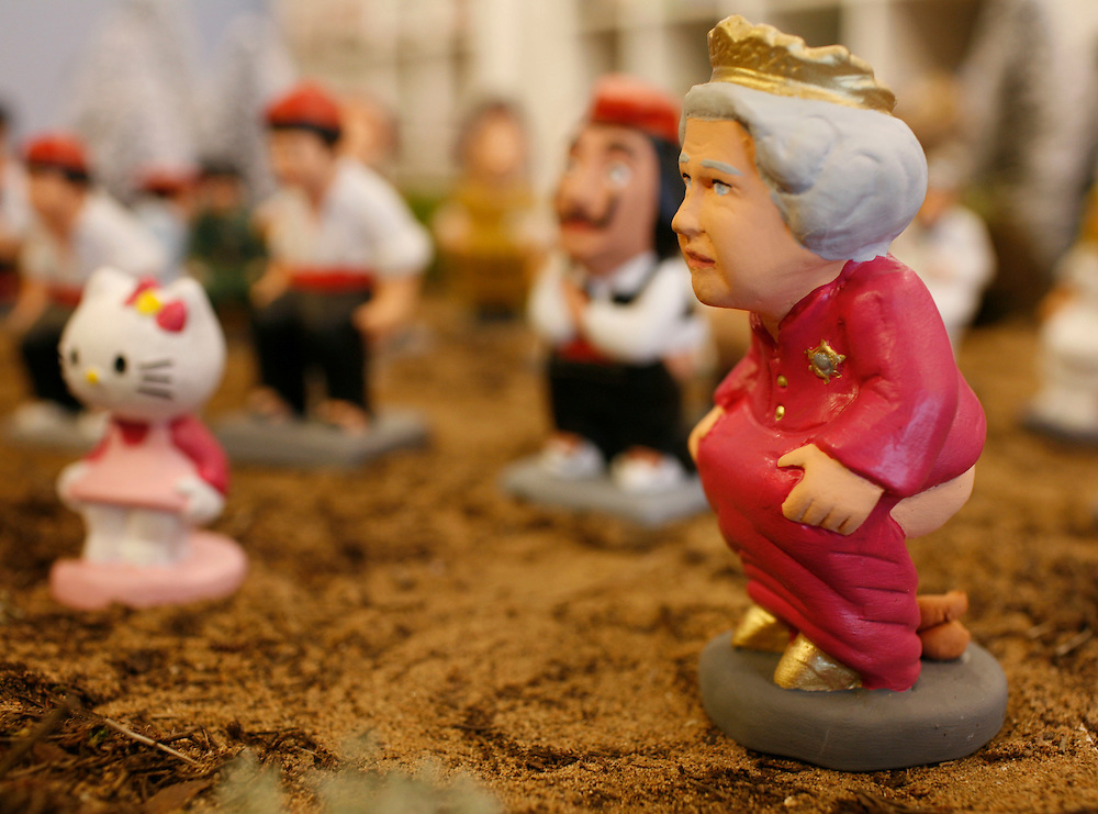 "Torroella de Mongri, Spain, 19 November 2009. .A company in Torroella de Montgrí (Girona, Spain) called ""caganer.com"" specialized in the production of ""caganers"" unveiled today  the new figures for Christmas as her majesty queen Elizabeth II..A ""Caganer"" is a small figure from Catalonia, usually made of fired clay,  and depicted as squating person in the act defecating. .""Caganer"" is Catalan for pooper. It fomrs part of one of the typical figures of  the manger or ""Nativity"" scene together with Mary, .Joseph and the baby Jesus but hidden in a corner. It is a humorous figure, originally portraying a peasant wearing a .barretina (a red stocking hat), and seems to date from the 18th century when it  was believed that the figure's depositions  .would fertilize the earth to bring a properous year. With  the course of the time, the original  personage of this pooping figure .was  substituted with personalities from the political and sports world and other famous personalities."