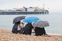 © Licensed to London News Pictures. 28/05/2017. Brighton, UK. Members of the public brave the grey clouds to spend some time on the beach in Brighton and Hove on the Bank holiday weekend as the occasional rain shower hits the seaside resort. Photo credit: Hugo Michiels/LNP