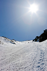Spring skiers climb the headwall of King Ravine in New Hampshire's White Mountains.  King Ravine is a glacial cirque on the north side of Mount Adams.  Backcountry skiing.