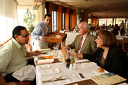 Ala'a Al-Aswany has lunch with Mark Linz and Nabila Akl, the director and promotions manager for his local publishers, The American University in Cairo Press in Cairo, Egypt on April 4, 2008.  Al-Aswany is a prominent Egyptian writer and founding member of the political movement Kefaya. Trained as a dentist in Cairo and Chicago, Al-Aswany has contributed numerous articles to Egyptian newspapers on literature, politics, and social issues. His second novel, The Yacoubian Building, an ironic depiction of modern Egyptian society, has been widely read in Egypt and throughout the Middle East. It was translated into English and was adapted into a film (2006) and a television series (2007) of the same name. Chicago, Al-Aswany's latest novel, is set in the American city where he had attended college.