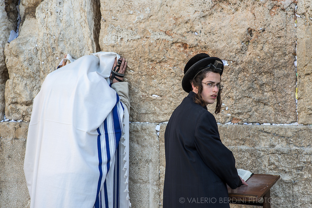 Morning prayer at the Western Wall. A man fully covered in a tallit shawl, with an arm tefillin wrapped on his right hand. A boy wears the head tefillin, or &quot;shel rosh&quot;, placed above the forehead. The Torah commands that this set of small black leather boxes containing scrolls of parchment inscribed with verses from the Torah,  should be worn to serve as a sign and remembrance that God brought the children of Israel out of Egypt. &quot;And it shall be for a sign for you upon your hand, and for a memorial between your eyes, that the law of the LORD may be in your mouth; for with a strong hand did the LORD bring you out of Egypt.<br /> &mdash;Exodus 13:9&quot;
