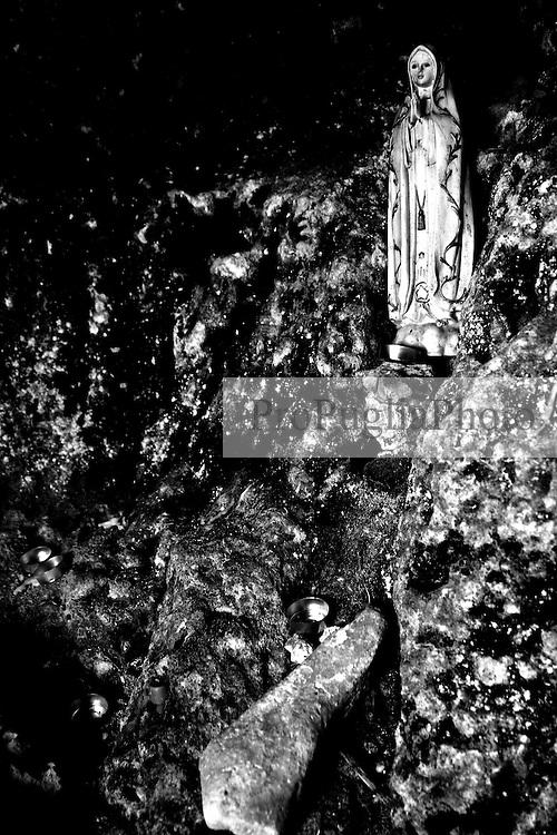 Reportage sul comune di Alessano per il progetto propugliaphoto..Una statuetta raffigurante la madonna all'interno di in una grotta..Macurano è un villaggio rupestre considerato un luogo di scambio e commercio, simbolo della cultura dell'olio per la presenza ad oggi di alcune tracce nelle grotte e di frantoi funzionanti nella zona. L'insediamento è caratterizzato da una serie di grotte sia naturali che scavate nel calcare, cisterne per la raccolta dell'acqua, sistemi di canalizzazione che scendono da Montesardo, viottoli, scalette e vie più larghe con antiche tracce di carri..Si ritiene che in questo sito, un vero e proprio centro abitato ben organizzato distante circa quattro km dalla costa, i monaci basiliani scappati dall'oriente in seguito alla lotta iconoclasta, trovarono rifugio e si dedicarono all'agricoltura..L'area del villaggio rupestre fu sicuramente sfruttata in epoche successive, lo prova l'esistenza di ben tre masserie di cui una fortificata e i resti di una serie di costruzioni che fanno parte dei numerosi esempi di architettura rurale presenti in questo territorio. .Il complesso masserizio, denominato Macurano, edificato probabilmente nel Cinquecento include la Masseria di Santa Lucia e la cappella di Santo Stefano. La Masseria è dominata dal nucleo originario, ovvero dalla torre cinquecentesca coronata da beccatelli a sostegno del parapetto aggettante del terrazzo sommitale.