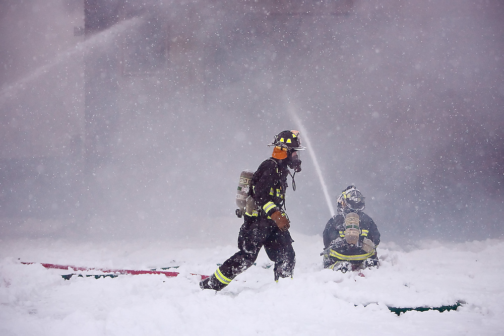 JEROME A. POLLOS/Press..A Northern Lakes firefighter trudges through the snow to the other side of a building that was destroyed in the Warren K Industrial Park in Hayden.
