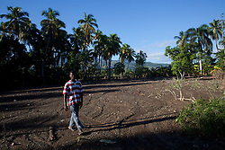 Jackson Bouqet, 24, walks through over mud in a field that was destroyed by Hurrican Sandy. Before the storm this field was filled with many crops, such as plantain and sugar cane. Hurricane Sandy brought heavy flooding to the region , destroyed crops and livestock and will seriously hinder farmers' abilities to grow food in the future.