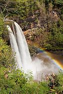 A rainbow appears in the mist generated by Wailua Falls, Kauai, HI