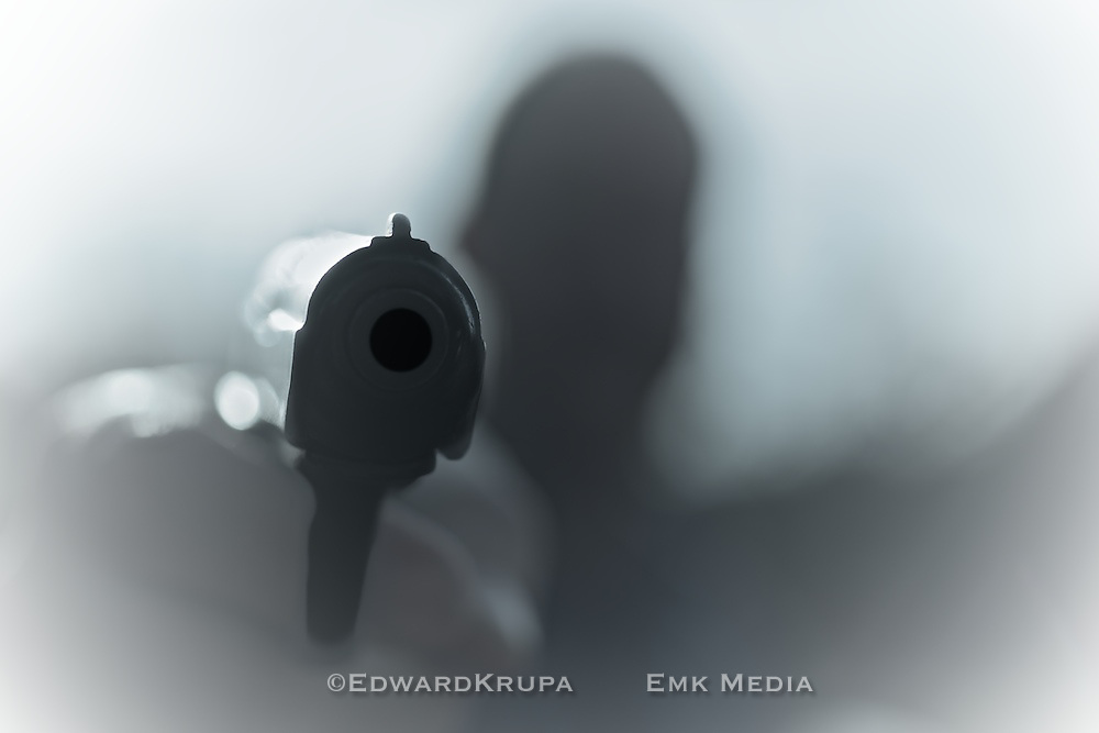 Point blank handgun held by out of focus silhouetted man.