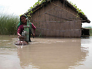 Jahana Begum draws drinkingwater from a submerged hand pump near her inundate house by floodwaters at Sialmari village, about 329 kilometers southwest of Gauhati, the capital city of Northeastern Indian state, Assam, Monday, June 28, 2004. ..Floodwaters of the Asia'a one of the largest river, Brahmaputra and its 35 tributaries have affected more than one million in all of Indian subcontinent and disrupted communication in many parts of the India and Bangladesh, sources said.  (AP Photo/ Shib Shankar Chatterjee).