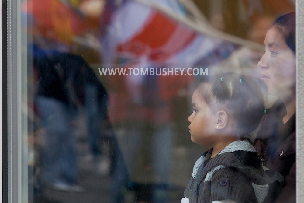 Middletown, New York - A woman and child watch from inside a building as members of St. Joseph's Church march through the city during the festival of Nuestra Senora de Guadalupe on Sunday, Dec. 9, 2012.
