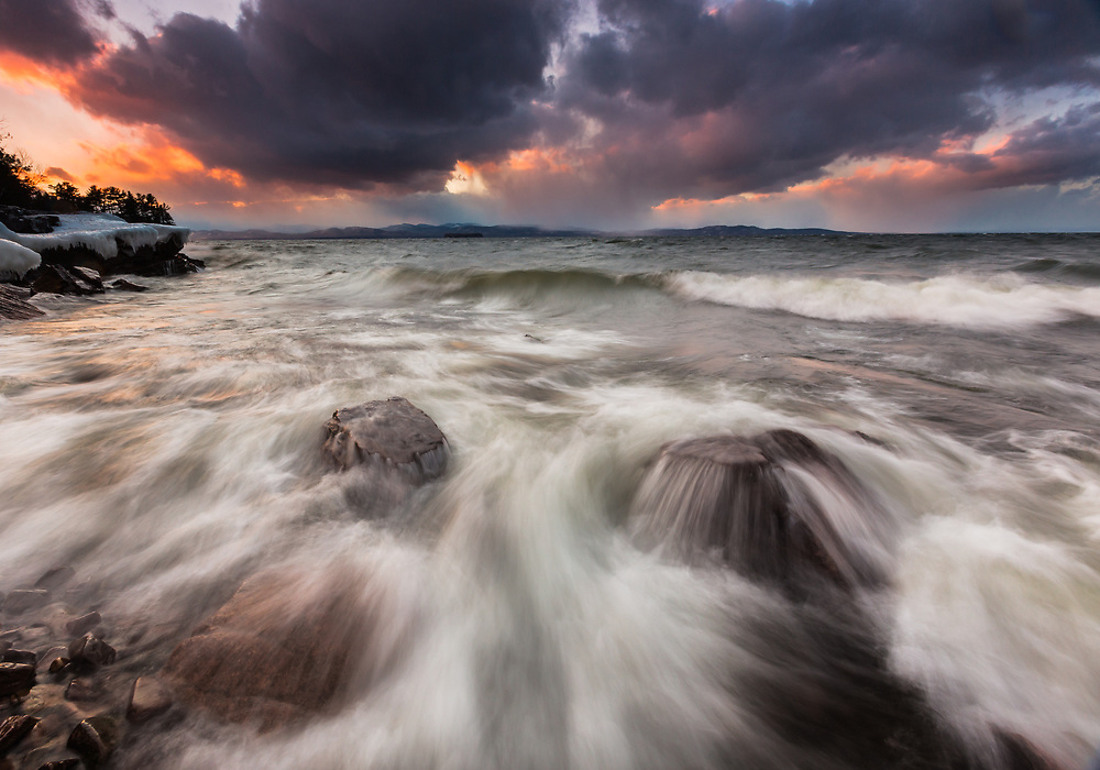 A long expsure captures the dynamic, crashing waves along Lake Champlain in Vermont during a stormy sunset.