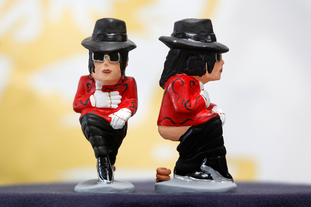 "November 10,  2010. A company in Torroella de Montgrí (Girona, Spain) called ""Caganer.com"", which specializes in the production of ""caganers"", unveiled today its new figurine for Christmas, Michael Jackson, Josn Lennon or prince Charles. .A ""Caganer"" is a small figure from Catalonia, usually made of fired clay, which depicts as squatting person in the act defecating..""Caganer"" is Catalan for pooper. It forms part of one of the typical figures of the manger or ""Nativity"" scene together with Mary, Joseph and the baby Jesus but hidden in a corner. It is a humorous figure, originally portraying a peasant wearing a ""barretina"" (a red stocking hat), and seems to date from the 18th century when it was believed that the figure's deposits would fertilize the earth to bring a prosperous year. With the course of time, the original personage of this pooping figure was substituted with personalities from the political and sports worlds and other famous personalities..Singer pop star Michael Jackson."