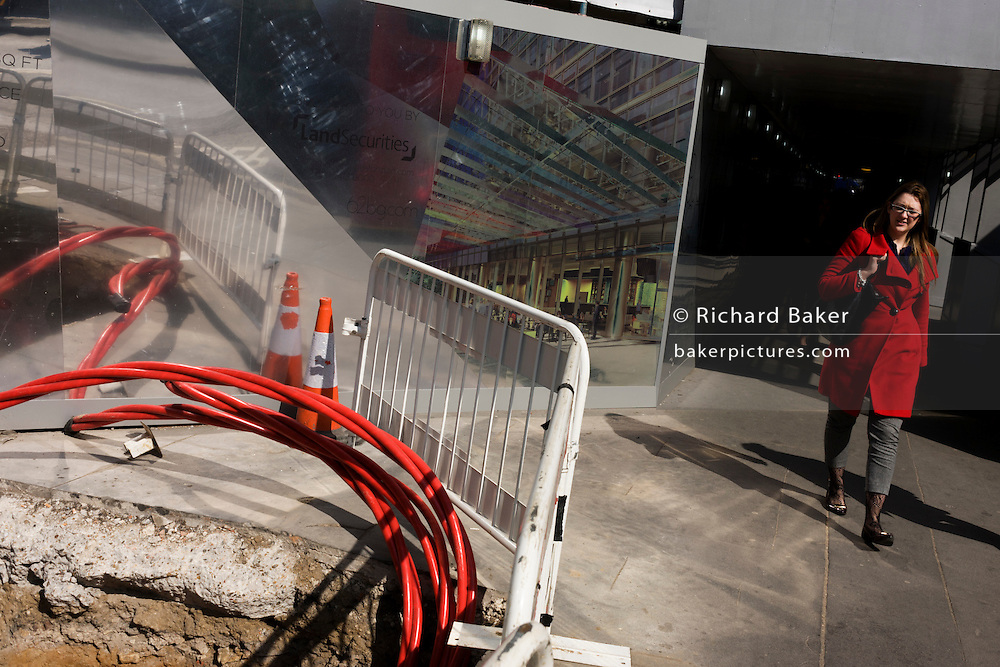 Pedestrian passes-by UK Power Networks high-voltage cable in central London with reflective corporate backdrop behind.