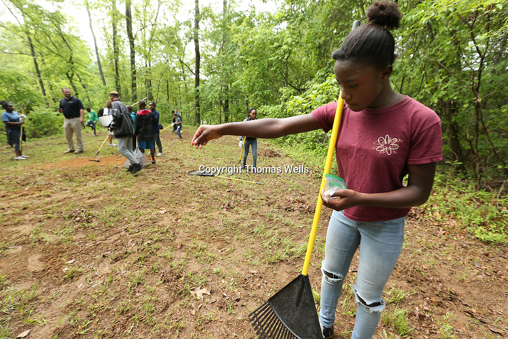 Kya Fields, 11, spreads new seeds at Tombigbee State Part as part of the Toyota's Adevnture Campout for youth from the Boys and Girls Club of North Mississippi on Saturday.