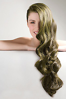 Beautiful woman with long green dyed hair against gray background