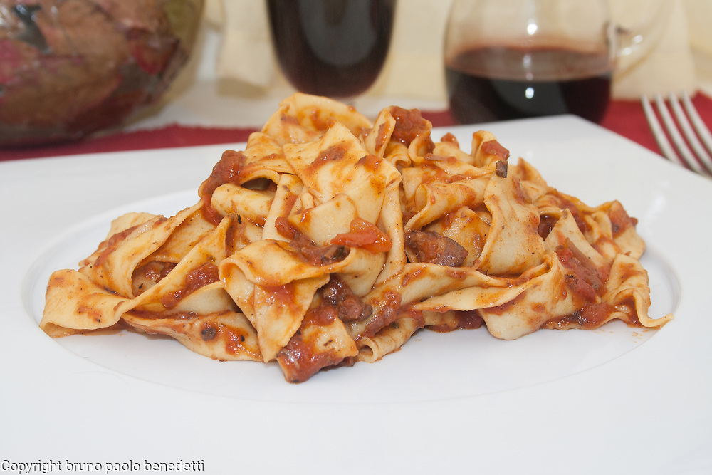 pappardelle pasta with wild boar sauce side view close-up on white dish and red wine on blured background,italian traditional food