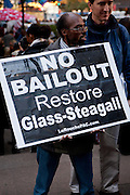 "An African-American man from the LaRouche PAC carries a large sign reading ""No bailout restore Glass-Steagall"""