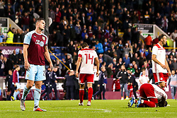 Kevin Long of Burnley cuts a frustrated figure as Olympiakos celebrate victory - Mandatory by-line: Robbie Stephenson/JMP - 30/08/2018 - FOOTBALL - Turf Moor - Burnley, England - Burnley v Olympiakos - UEFA Europa League Play-offs second leg