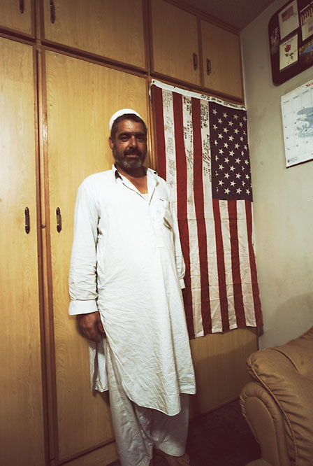 A man poses alongside an American flag in the home of a drug lord who is responsible for the trafficking of vast quantities of heroine and cocaine within the tribal regions at the Smuggler's Bazaar, Khyber-Pakhtunkhwa, Pakistan on 25th Sep, 2007. Supposedly he has close affiliations with the CIA and is considered a partner within the region on the US War on Terrorism..