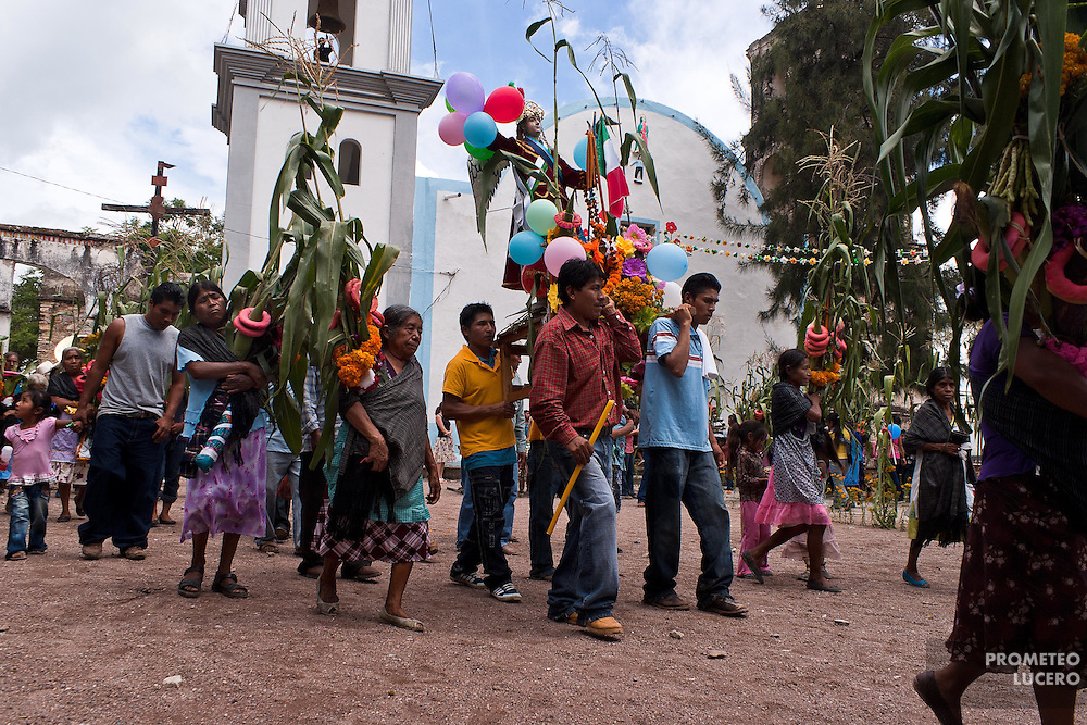 Men and women meet together in the afternoon after the ritual of the dance has finished. Carrying the image of San Miguel Arcángel, they walk in the yard of the church and continue the ritual sharing the food in their homes. (Photo: Prometeo Lucero)