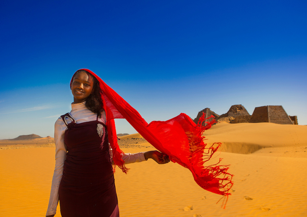 Meroe, Sudan, young Sudanese woman in front of the pyramids and tombs in Royal Cemetery.