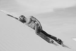 hot muscular shirtless man on a sand dune